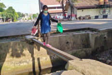 A woman carefully crosses a makeshift bridge placed over a gutter behind the Kampung Rambutan bus terminal in East Jakarta on July 1. The bridge lead to the terminal's back gate. Some commuters prefer this precarious path as it is closer than the terminal's main gate. JP/P.J.Leo