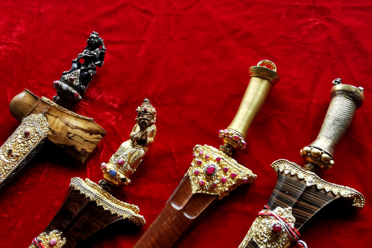 Deadly artistic: Elaborately adorned hilts and sheaths of ceremonial kris.