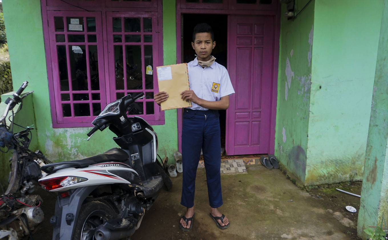 SMP 4 Bawang student Khoerul Risal poses in front of his house in Batang regency, Central Java with his weekly assignments he just received from his teacher. Antara/Harviyan Perdana Putra