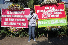 A senior high school student stands in front of flower boards at City Hall protesting alterations to the public school enrollment system in Central Jakarta on July 6. Many parents are unhappy with the enrollment system, which prioritizes age over performance. JP/Dhoni Setiawan
