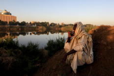 """Mohamed Ahmed al Ameen, 55, a brick maker, drinks a cup of tea as he sits on the edge of the Blue Nile near an open-air factory on Tuti Island, Khartoum, Sudan, February 14, 2020. """"I consider the Nile to be something that I have never parted with, ever since I was born"""", Ameen said. """"I eat from it, I farm with it. I also extract these bricks from it ? My whole source of income is from the Nile."""" Reuters/Zohra Bensemra"""