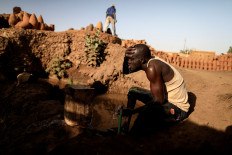 David Plantino, 35, a pottery maker from South Sudan, cools himself down with water from the Nile river, next to a workshop in an area known as the 'Potters Village' in Alqamayir, Omdurman, Sudan, February 16, 2020. Reuters/Zohra Bensemra