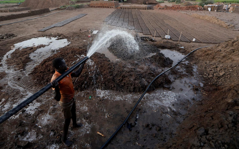 Zaki El-Dine, 24, a brick-maker, pours water from the Nile river onto a patch of mud to make bricks on Tuti Island, Khartoum, Sudan, February 12, 2020. Reuters/Zohra Bensemra
