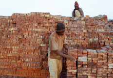 """Mustapha, 60, a brick maker, piles up bricks after removing them from a kiln at an open-air factory on Tuti Island, Khartoum, Sudan, February 20, 2020. """"I fear that we will not gain any advantage from the Dam that Ethiopia is building. I am not an expert but I think the amount of water as well as mud will decrease. We usually get the mud when the Nile overflows"""", said Mustapha.Reuters/Zohra Bensemra"""