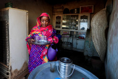 """Ibtissam, 46, whose husband Mutasim al-Jeiry is a pottery maker, carries a tray out of the kitchen at their home in an area known as the 'Potters Village' in Alqamayir, Omdurman, Sudan, February 18, 2020. """"Our life depends on the mud of the Nile, without it we will not eat"""", said Ibtissam. Reuters/Zohra Bensemra"""