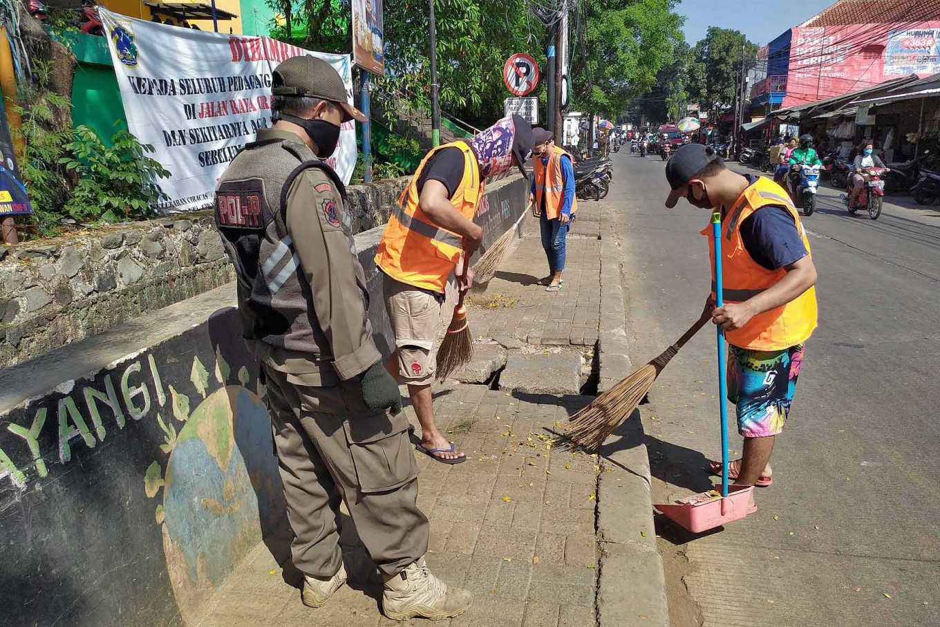 A Public Order Agency (Satpol PP) officer supervises three men as they sweep a sidewalk at Ciracas Market in East Jakarta on July 17. The three were obligated to take part in the act of community service after violating COVID-19 health protocols. - JP/P.J. Leo