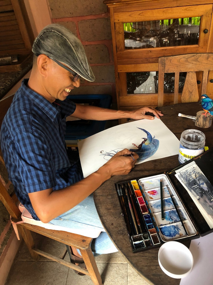 Aluysius Sulistianta works on a design using watercolors.
