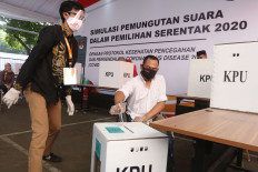 An election official helps a voter with a disability take part in a simulation of the 2020 simultaneous regional elections in the front yard of the General Elections Commission (KPU) headquarters on July 22. The KPU implemented COVID-19 protocols while holding the voting simulation. JP/Dhoni Setiawan