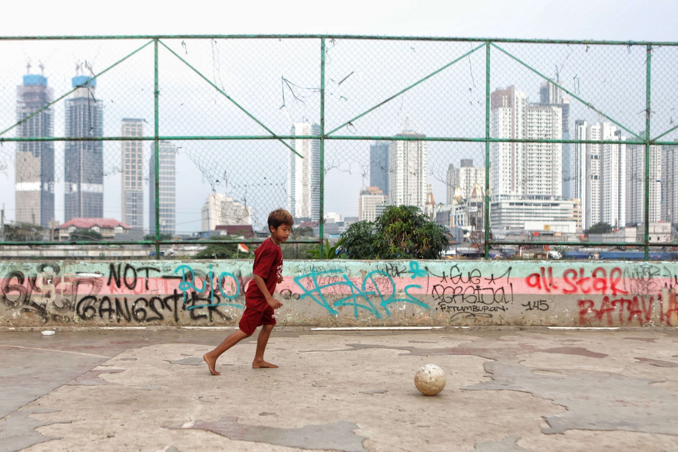 A boy plays soccer at a playground near the West Flood Canal in Jakarta on July 21. London-based NGO Save the Children states that around 9.7 million children around the world have potentially been affected by school closures and are at risk of permanently dropping out of school because of the COVID-19 pandemic. JP/Seto Wardhana