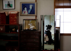 Ikuko, who is a geisha, sits in front of a mirror in her living room as she gets ready to work at a party being hosted by customers at a luxury restaurant, where she will be entertaining with other geisha, during the coronavirus (COVID-19) outbreak, in Tokyo, Japan, June 23, 2020. Reuters/Kim Kyung-Hoon