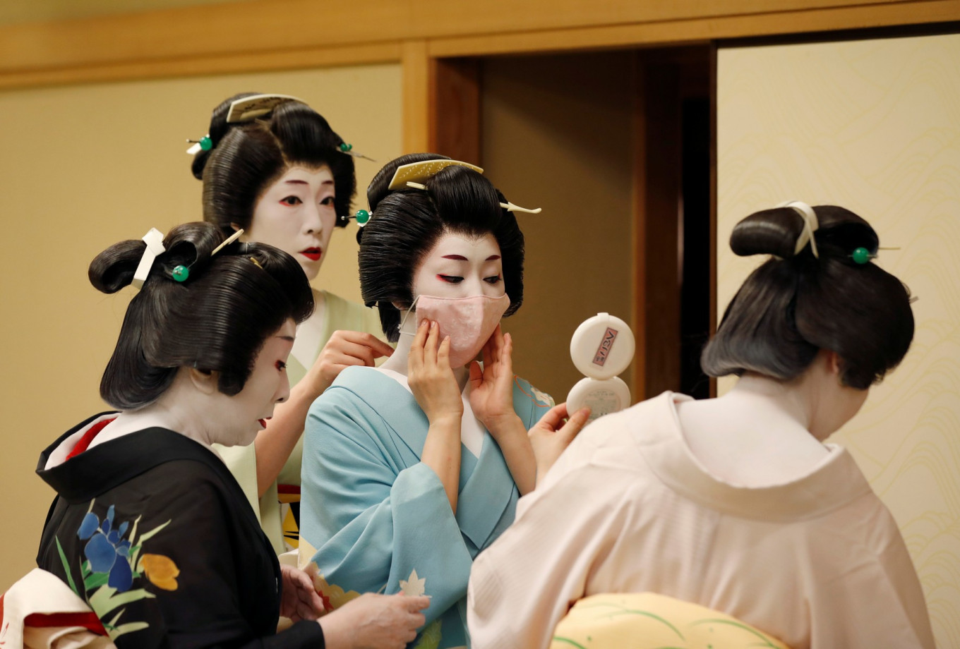 Senior geisha help Koiku put on a protective face mask to have a portrait photo taken of her wearing one for Reuters, before working at a party being hosted by customers, where she will entertain with other geisha, at Asada, a luxury Japanese restaurant, during the coronavirus disease (COVID-19) outbreak, in Tokyo, Japan, June 23, 2020. Reuters/Kim Kyung-Hoon