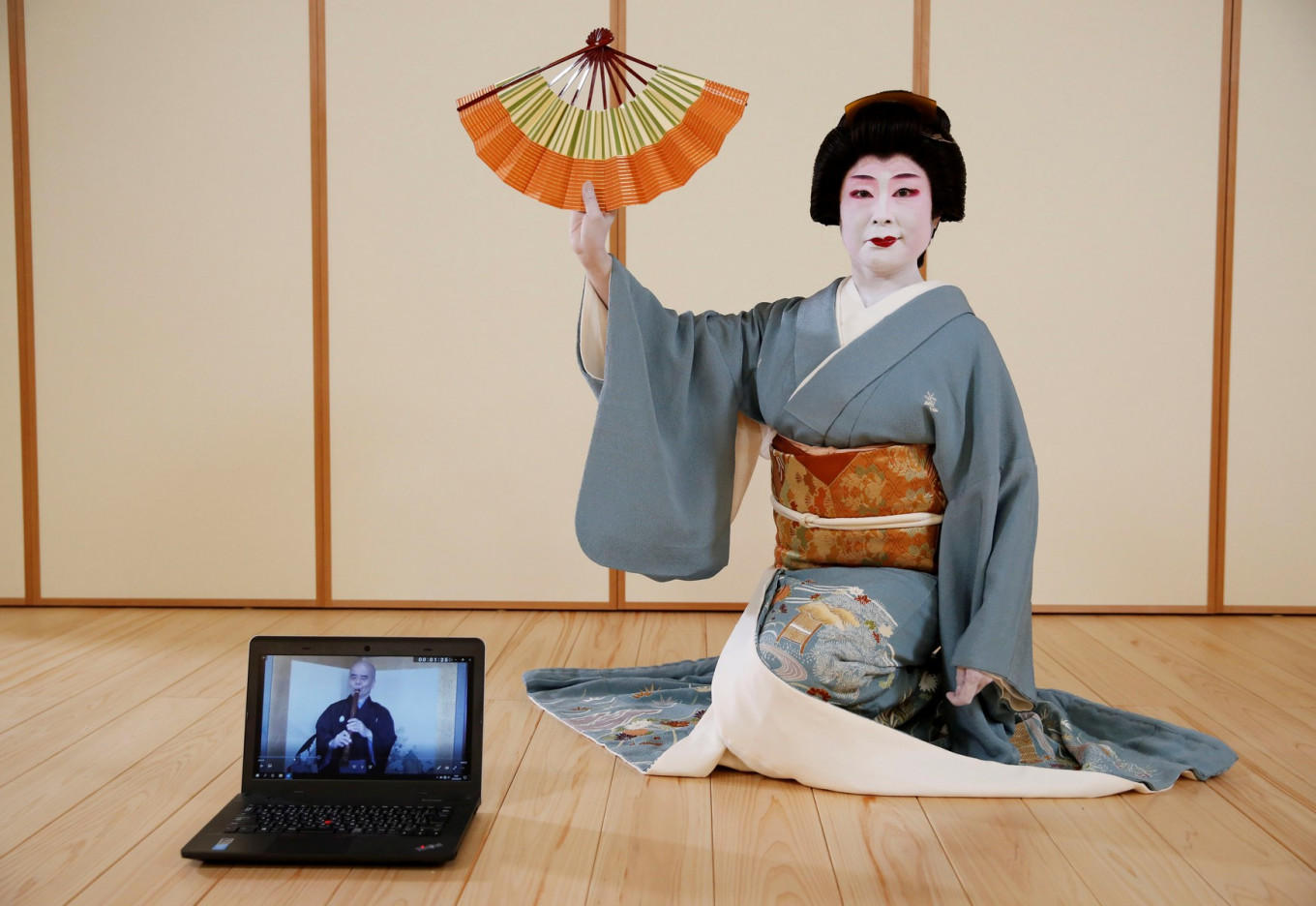 Tokijyo Hanasaki, a jiutamai dancer, poses for a photograph behind a laptop playing a musical performance which was filmed in advance in order to avoid physical contact, to accompany  Hanasaki's dance performance for a film being made that is supported by the Tokyo Metropolitan government in order to support artists during the coronavirus disease (COVID-19) outbreak, at a studio in Tokyo, Japan, June 29, 2020. Reuters/Kim Kyung-Hoon