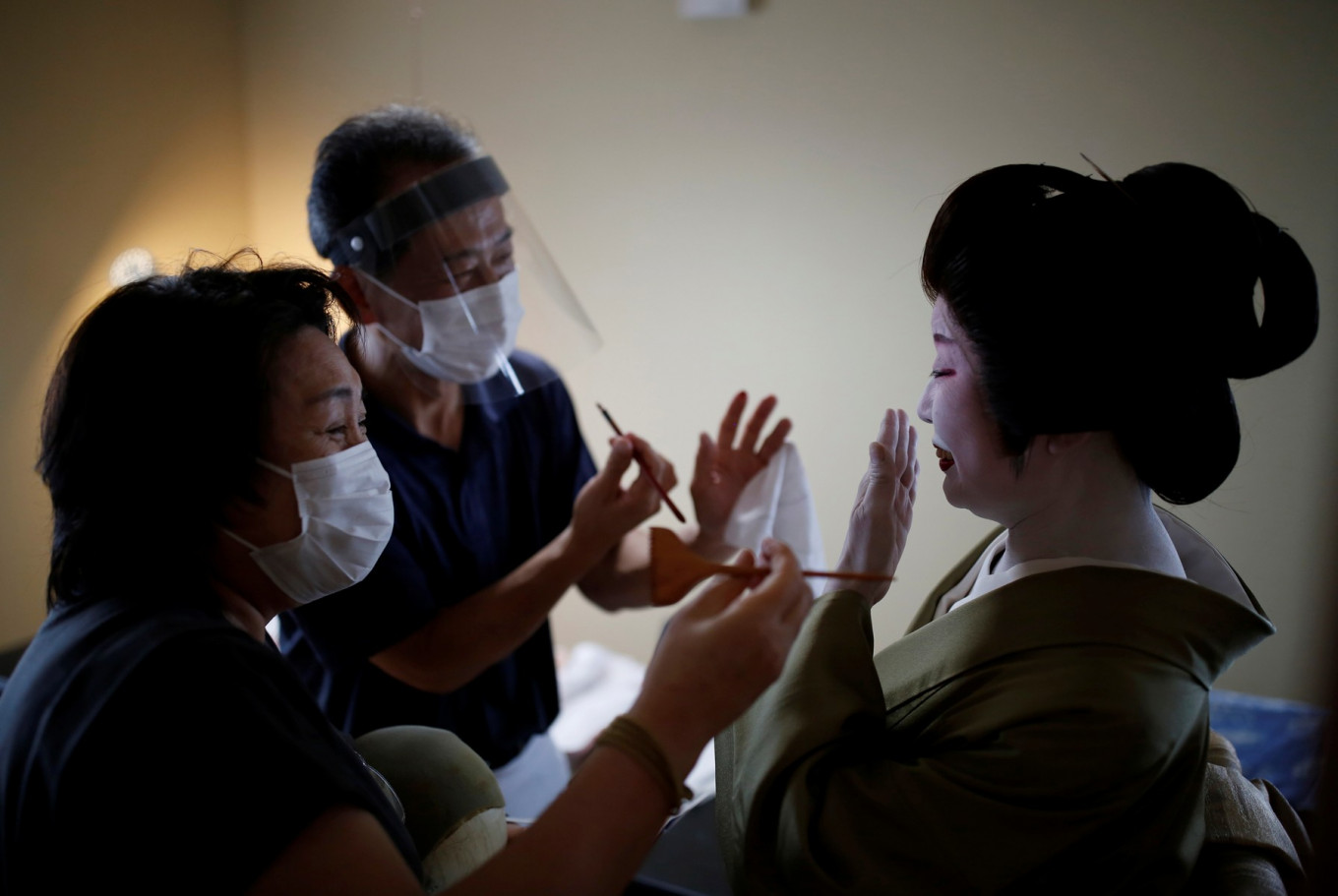 "Mitsunaga Kanda, a makeup artist and Yurie Hatanaka, a wig stylist, wear protective face masks and face shields as they work on Tokijyo Hanasaki, a jiutamai dancer, before he dances for a film being made that is supported by the Tokyo Metropolitan government in order to support artists during the coronavirus disease (COVID-19) outbreak, at a studio in Tokyo, Japan, June 29, 2020. ""Every single one of my events has been cancelled"", said Kanda. ""We touch their skin and their face, all over, and while we don't talk we're very close - something we're very aware of now."" Reuters/Kim Kyung-Hoon"