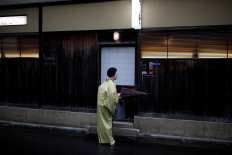 Koiku, who is a geisha, folds a traditional umbrella made out of oil paper, as she arrives at a restaurant where she will work at a party hosted by her customers, where she will entertain, during the coronavirus disease (COVID-19) outbreak, in Tokyo, Japan, July 13, 2020. Reuters/Kim Kyung-Hoon
