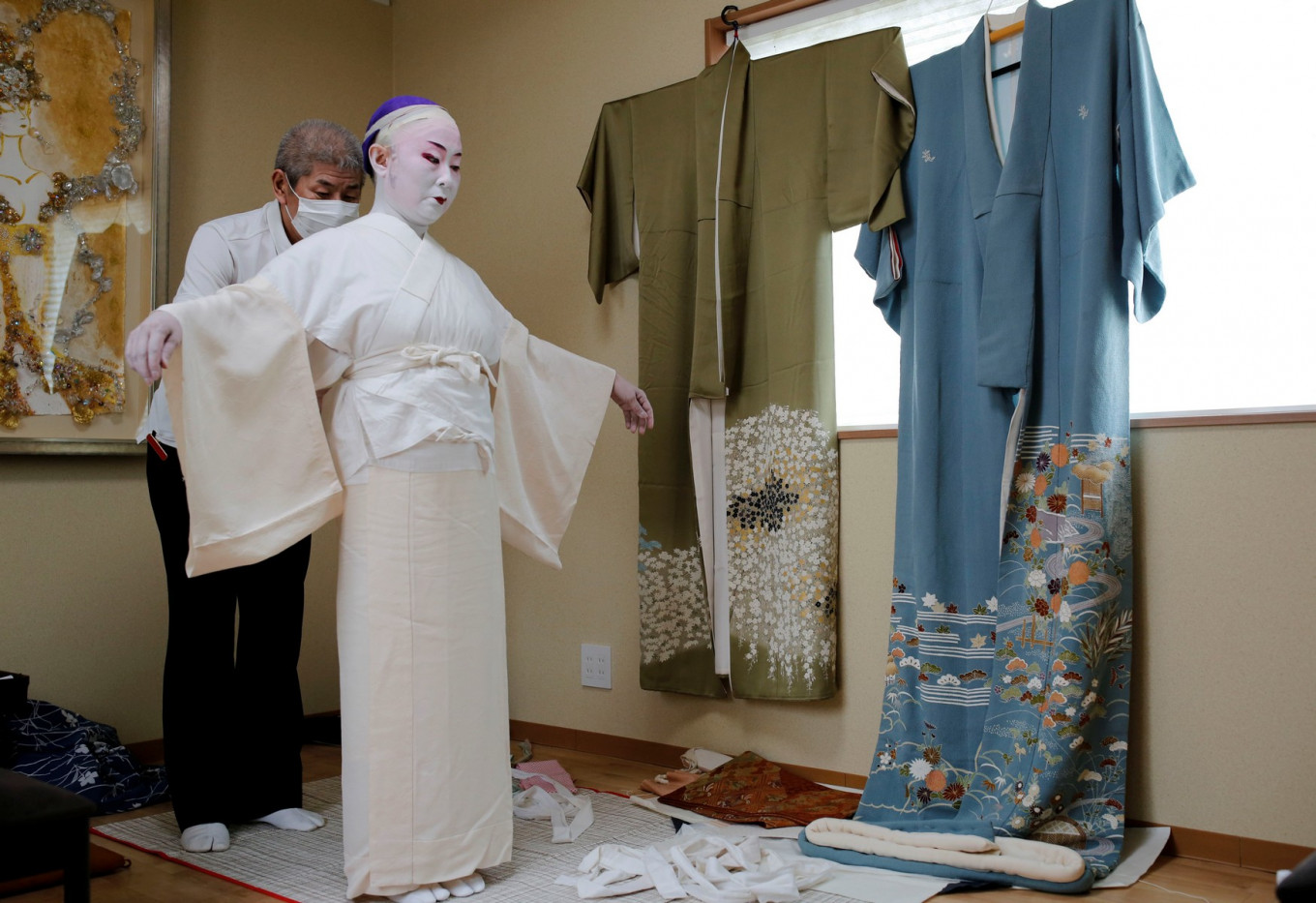 Shoichi Sanagashi, a kimono dresser, wears a protective face mask as he dresses Tokijyo Hanasaki, a jiutamai dancer, before Hanasaki is recorded dancing for a film supported by the Tokyo Metropolitan government in order to support artists during the coronavirus disease (COVID-19) outbreak, at a studio in Tokyo, Japan, June 29, 2020. Reuters/Kim Kyung-Hoon