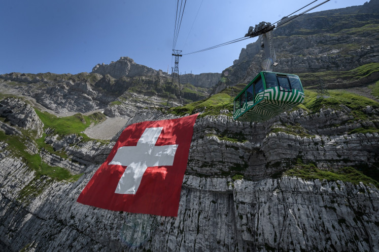 A picture taken on on July 31, 2020 near Schwagalp, eastern Switzerland, shows a huge 6,400 square meters Swiss flag hanging on the rock face of mountain Saentis on the eve of Swiss national day.   (AFP/Fabrice Coffrini).  Usage: 0