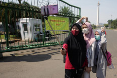 A group of girls take a selfie in front of the gate of the National Monument in Central Jakarta on July 26. Jakarta Deputy Governor Ahmad Riza Patria said the tourist site would remain closed to visitors as it was undergoing rearrangements amid the epidemic. JP/Wendra Ajistyatama
