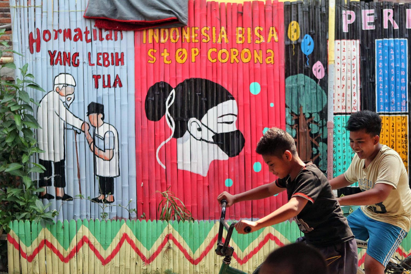Children play near a coronavirus-themed mural at a playground in Kalipasir, Jakarta, on July 28.  Indonesia has recorded the highest number of coronavirus cases in Southeast Asia with 111,455 cases as of Sunday. JP/Seto Wardhana