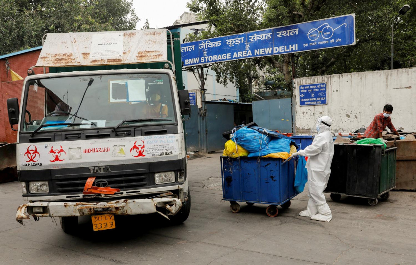 A medical staff member wearing personal protective equipment (PPE) pushes a trolley containing medical waste bags to a Bio-Medical Waste storage area, during the coronavirus disease (COVID-19) outbreak, in New Delhi, India, July 17, 2020. Reuters/Adnan Abidi