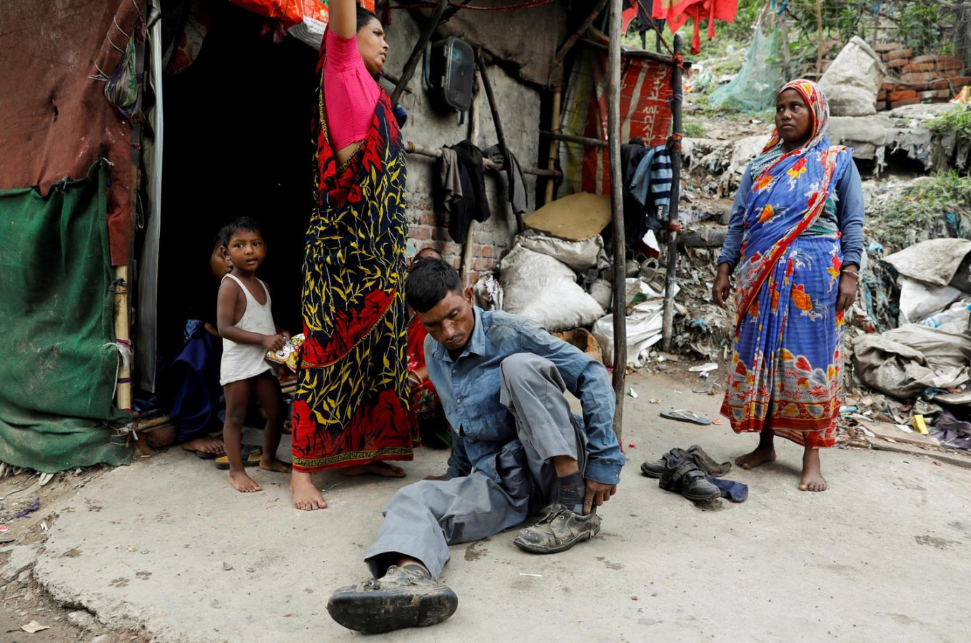 Mansoor Khan, 44, who works as a waste collector, puts on his shoes as he gets ready to look for recyclable materials from a landfill site next to his house, during the coronavirus disease (COVID-19) outbreak, in New Delhi, India, July 16, 2020. Reuters/Adnan Abidi