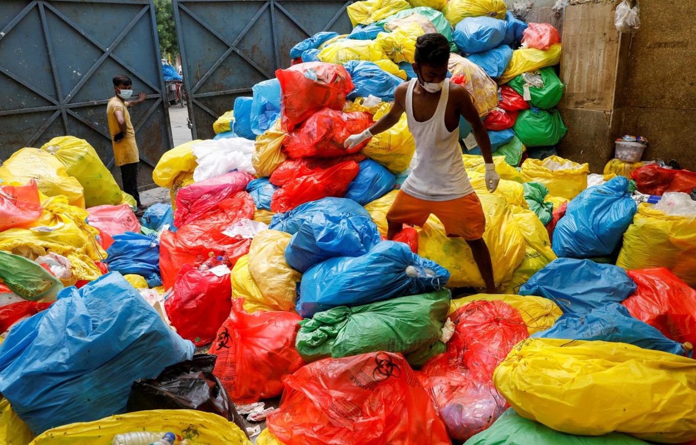 A waste collector walks over disposed medical waste bags inside a rubbish dump outside a hospital, during the coronavirus disease (COVID-19) outbreak, in New Delhi, India, July 17, 2020. Reuters/Adnan Abidi