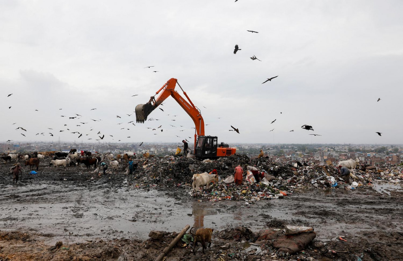 Waste collectors look for recyclable materials at a landfill site, during the coronavirus disease (COVID-19) outbreak, in New Delhi, India, July 22, 2020. Reuters/Adnan Abidi