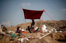 Latifa Bibi, 38, who is married to Mansoor Khan, a waste collector, shields herself from the sun, under a blanket with other waste collectors, at a landfill site during the coronavirus disease (COVID-19) outbreak, in New Delhi, India, July 9, 2020. Reuters/Adnan Abidi