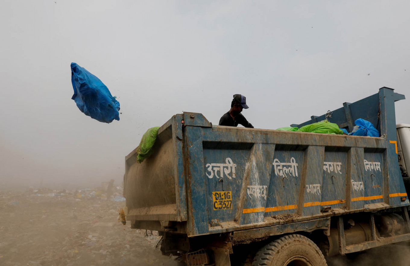 A waste collector goes through bags of rubbish as he throws them off the truck into the landfill site, during the coronavirus disease (COVID-19) outbreak, in New Delhi, India, July 15, 2020. Reuters/Adnan Abidi