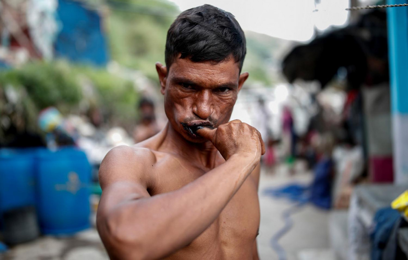 Mansoor Khan, 44, a waste collector, uses a piece of charcoal to clean his teeth, outside his home which is next to a landfill site, during the coronavirus disease (COVID-19) outbreak, in New Delhi, India, July 16, 2020. Reuters/Adnan Abidi