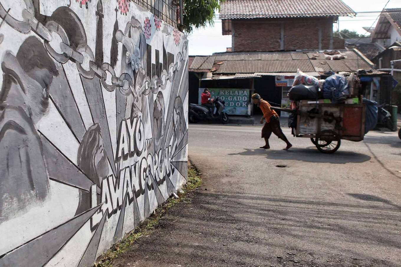 An informal waste sorter walks past a COVID-19-themed mural in Rempoa, South Jakarta, on Aug. 2. Jakarta accounts for 19.7 percent of the country's COVID-19 cases, behind only East Java in its provincial tally. JP/Seto Wardhana