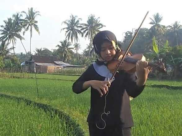Working from home: Violinist Arum Kusuma Dewi performs from the serenity of a field near her home.