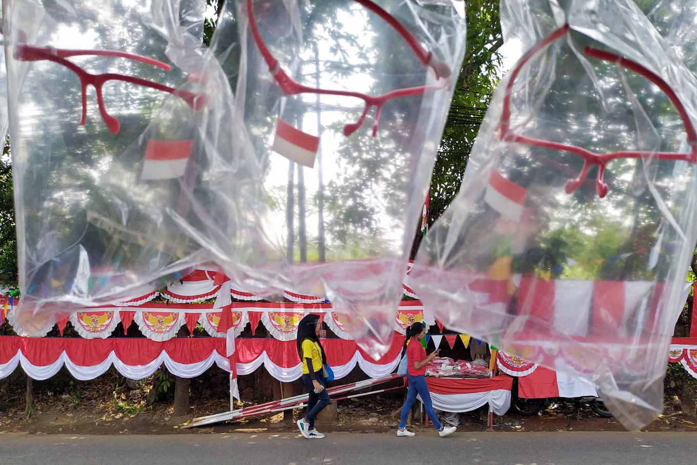 Two women pass by Independence Day-themed decorations in Depok, West Java, on Aug. 10. Although the pandemic still shows no signs of slowing down, some communities are still eager to hold festive Independence Day celebrations.