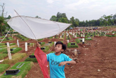 A boy plays with a kite in the Pondok Ranggon Public Cemetery in East Jakarta on Aug. 14. With a limited amount of open space, many children in Jakarta are forced to play in some unusual places, including in this cemetery, which has served as the final resting place of many COVID-19 victims.