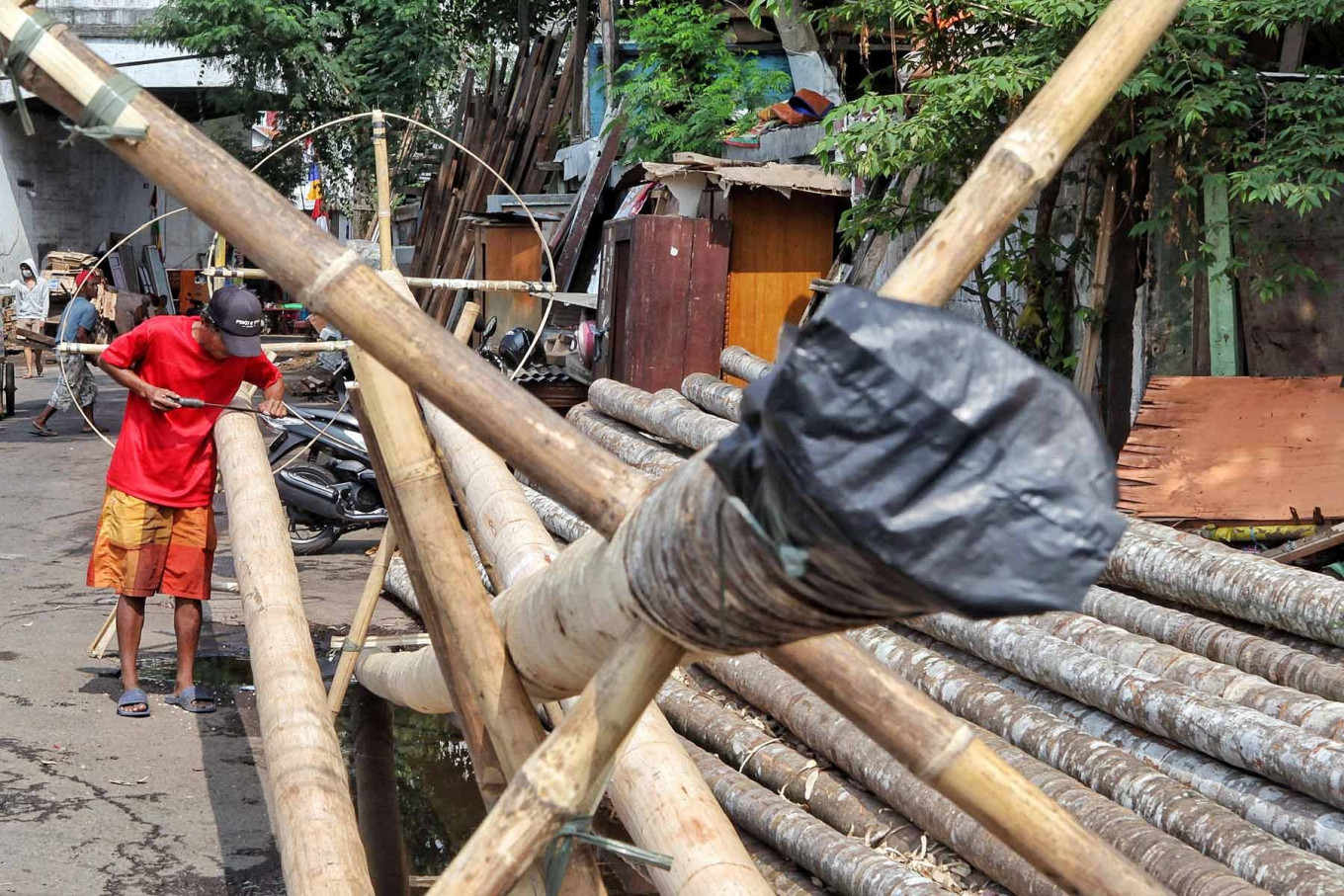 Aep, 50, shaves bamboo for panjat pinang (pole climbing) competitions, which are usually held during Indonesia's Independence Day celebrations, in Manggarai, Jakarta, on Aug. 13. Pinang bamboo craftsmen have seen a loss in income after the Jakarta administration restricted events that attract crowds amid the surge in COVID-19 cases. While in normal years, a craftsman can sell up to 50 pinang, this year they haven't been able to sell any.
