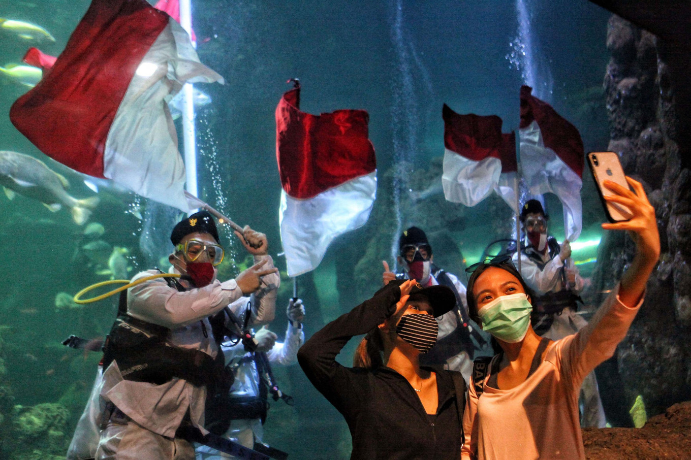 Deep dive: Visitors take a wefie as divers hold a rehearsal of an underwater flag-waving ceremony at Seaworld Indonesia in Ancol, North Jakarta, on Saturday. The annual event was held to commemorate the 75th anniversary of Indonesia's independence. JP/Seto Wardhana