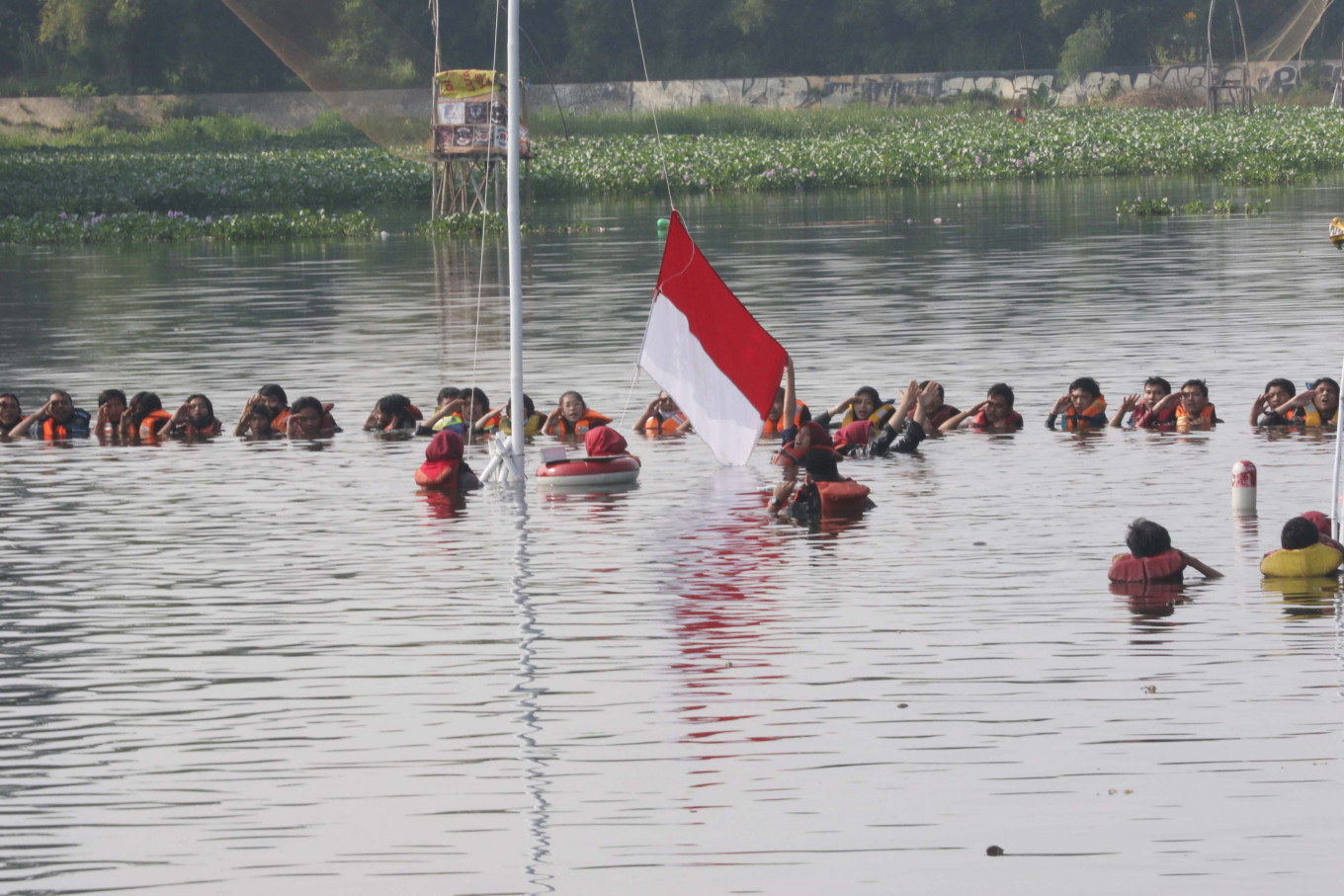 Aquatic anniversary: Environmental activists hold a flag hoisting ceremony in Muara 7 Lake in Pamulang, South Tangerang on Monday to mark the country's Independence Day and promote the preservation of lakes across the country. JP/Dhoni Setiawan