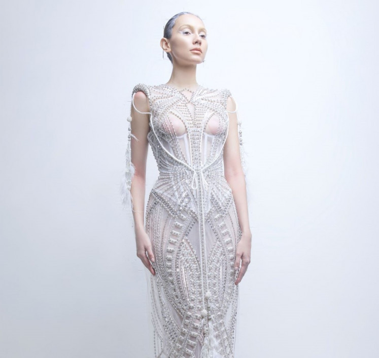 Lady in white: Tex Saverio's designs hint at ethereal grace, with intricate detailing cascading down a floor-length silhouette.