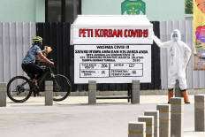 A cyclist rides by a fake coffin guarded by a mannequin dressed in protective gear in Kemang, South Jakarta, on Aug. 17. The display is part of a campaign to raise awareness about the dangers of COVID-19.  JP/Dhoni Setiawan