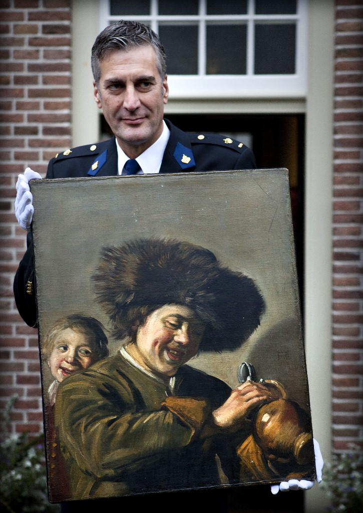 This photograph taken on November 3, 2011, shows District Chief of Alblasserwaard, Bart Willemsen showing the recovered painting 'Two Laughing Boys' by Frans Hals which was stolen from the Leerdam Museum in May 2011. Thieves have stolen the painting from a museum in the Netherlands, the third time it has been taken, police said on August 27, 2020.