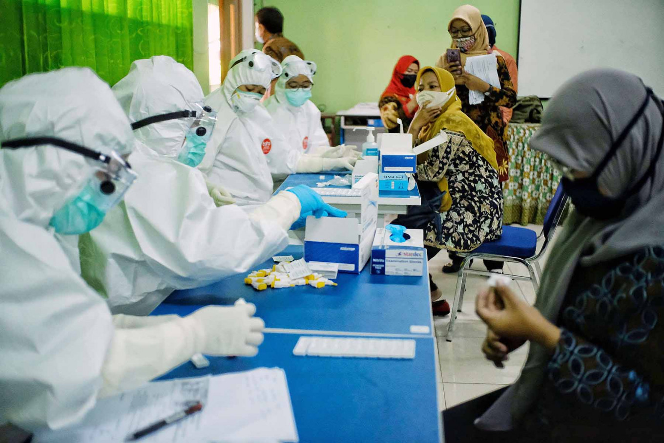 Health workers conduct COVID-19 rapid tests on teachers at SMP 3 state junior high school in South Tangerang, Banten, on Aug. 27. Authorities held rapid tests for middle school teachers in Ciputat, Tangerang, to trace the spread of COVID-19 and prevent further coronavirus outbreaks in the area. JP/Seto Wardhana