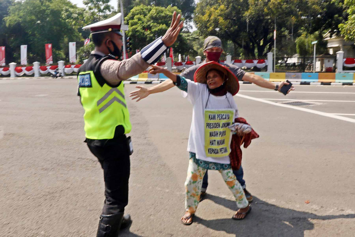 """A farmer attempts to enter the State Palace compound in Central Jakarta on Aug. 26 as dozens of others from Simalingkar and Sei Mencirim in Deli Serdang regency, North Sumatra, stage a rally to implore President Joko """"Jokowi"""" Widodo to help them regain their land, which they claim was seized by state-owned plantation company PTPN II. JP/Dhoni Setiawan"""