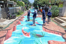 People take selfies by a street mural painted on Jl. Keuangan Raya in Cilandak, Jakarta, on Aug. 25. The mural was painted by sixteen painters from the Jakarta Artists Community. JP/Seto Wardhana