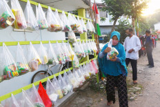 A woman collects a package of staple food containing rice, instant noodles and vegetables at the Villa Pamulang housing complex, South Tangerang, Banten, on Friday. Residents of the housing complex collect funds to buy 150 to 200 packs of food every Friday to be distributed to their neighbors in need. JP/Dhoni Setiawan
