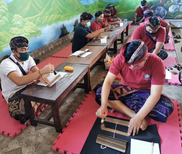 Team work: Members of Penyuluh Bahasa Bali work together to clean up lontar manuscripts owned by residents of Bulian.