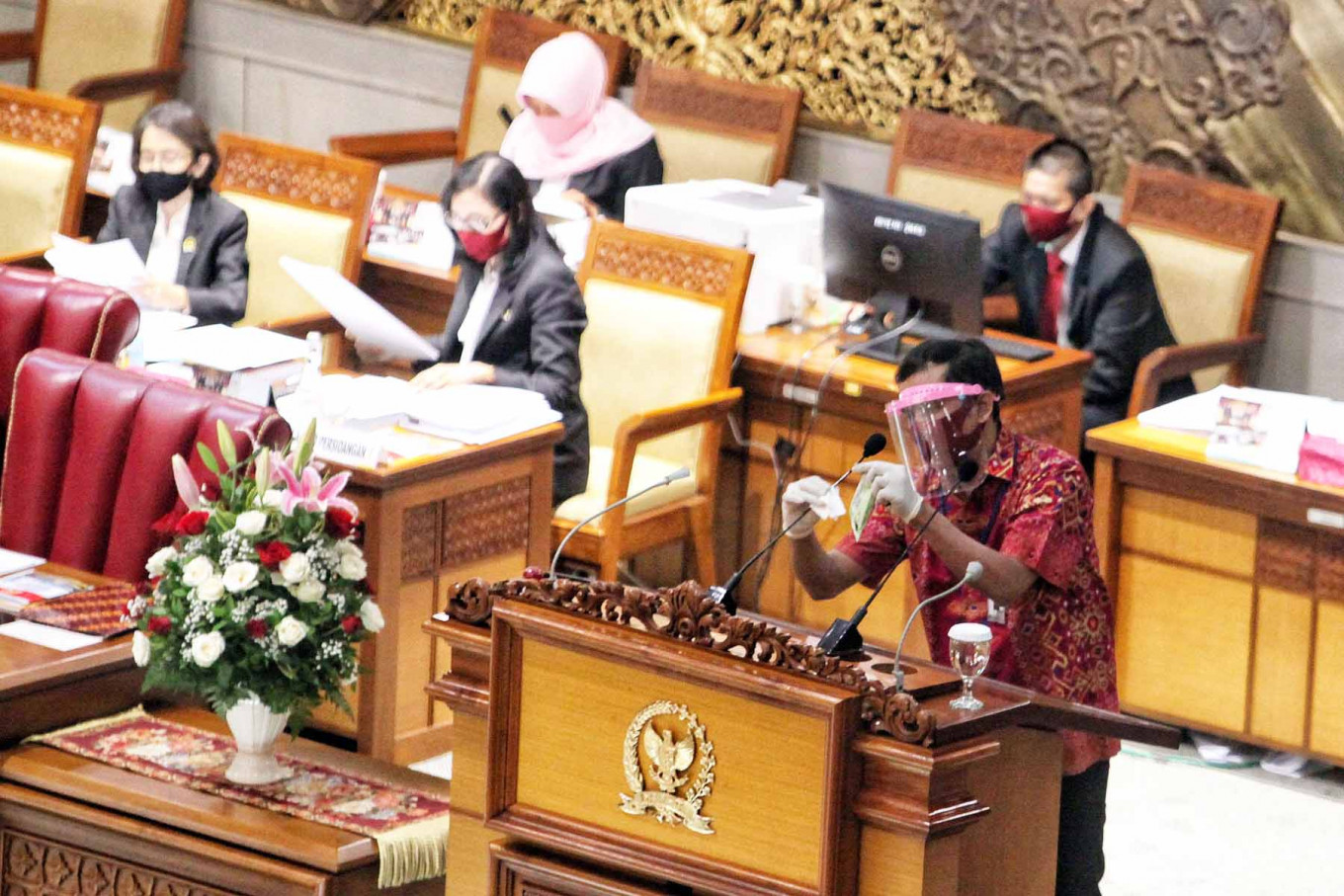 A staff member disinfects a microphone before a House of Representatives plenary session in Central Jakarta on September. 1. 2020. The session heard general views from party members on the draft 2021 state budget and endorsed a revision of the Constitutional Court Law. JP/Seto Wardhana