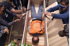 A man is made to lie in a coffin for failing to wear a face mask in Kalisari, East Jakarta, on Thursday, September 3. 2020. A joint team of Jakarta Public Order Agency (Satpol PP), police and military personnel handed down the controversial punishment to health protocol offenders in the area. The joint team eventually decided to stop the punishments following widespread criticism.  JP/P.J. Leo