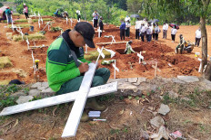 A grave digger writes the name of a deceased COVID-19 patient on a cross at Pondok Ranggon public cemetery, East Jakarta, on August. 31. 2020, while a burial proceeds in the background. Up to 40 people are buried in the cemetery every day. JP/P.J. Leo