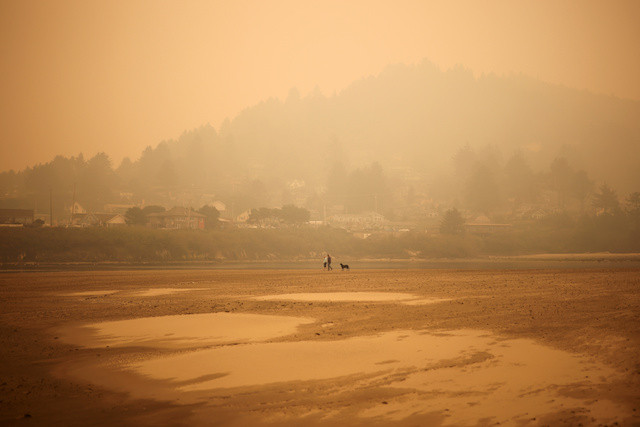 People walk by the Pacific Ocean coast as smoke from wildfires covers an area near Yachats, Oregon, US, Sept. 8, 2020.
