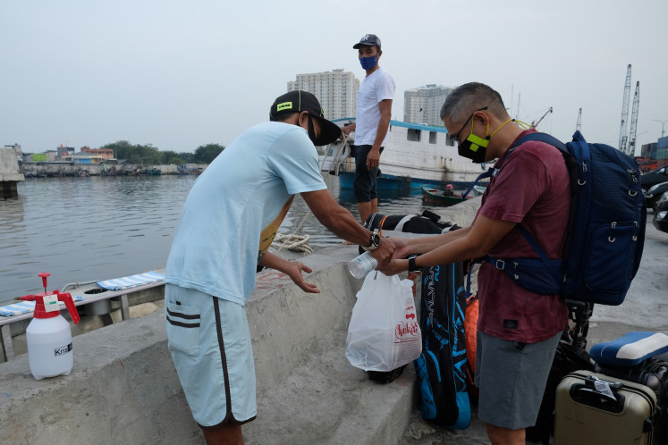 Keep it safe: The Benetta ship crew sprays disinfectant to the hands of diving trip participants.