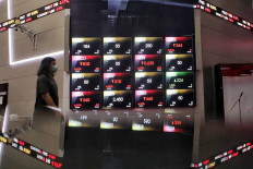 A man walks past an electronic board showing the movement of the Indonesian Composite index (IHSG) at the Indonesia Stock Exchange in Jakarta, Thursday, Sept. 10, 2020. JP/Seto Wardhana